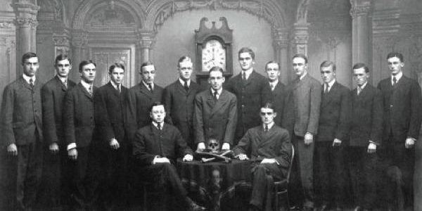 Skull & Bones: Der Orden hat ein privates Gruppenfoto von allen cohorts der Fünfzehn genommen. Posiert wird immer in der gleichen Weise, so dass menschliche Knochen zu sehen sind und eine alte Standuhr, die auf 8 Uhr gestellt ist. / Quelle: Wikipedia public domain