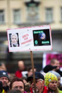 Demonstration mit einem Transparent, auf dem Greta Thunberg als Präsidentin gefordert wird / Quelle: Pexels, lizenzfreie Bilder, Markus Spiske: https://www.pexels.com/de-de/foto/stadt-menschen-strasse-manner-2058780/